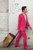 Young man in pink suit pulls hairy roller bag