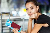 pretty businesswoman with air ticket at airport waiting for flight
