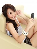 pic of handphone  - smiling young girl sitting on sofa and hold the handphone - JPG