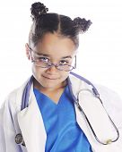 Closeup image of a young elementary girl smiling over her glasses and wearing scrubs, a lab coat and