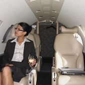 Businesswoman having a drink inside airplane