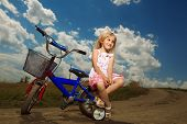 smiling little girl cycling on field