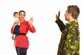 stock photo of goodbye  - Mother holding crying baby and say goodbye to her military husband which goes back to the army isolated on white background - JPG