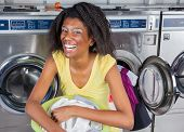 Portrait of cheerful young woman with laundry basket sitting at laundromat