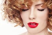 Close-up portrait of young beautiful woman with curly hair and red lipstick