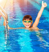 Closeup on little boy wearing swimming goggles in the pool, junior swimming competition, happy winner with raised up hand, summer time sport
