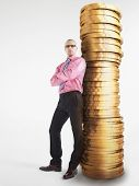 Full length of a confident male executive leaning against pile of coins on white background
