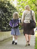 picture of schoolgirl  - Rear view of schoolgirl walking with mother on pavement - JPG