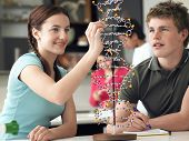 Happy teenage students examining DNA model and taking notes in science class