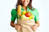 Image of big paper sack full of different fruits and vegetables in female hands