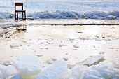 Icebound Chair Near Ice Hole In Frozen Lake
