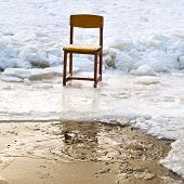 Icebound Chair On Edge Of Ice-hole In Frozen Lake