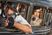 pic of tommy-gun  - Group of three 1920s era gangsters shooting from car window