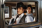 pic of tommy-gun  - A Sneering 1920s vintage gangsters inside automobile