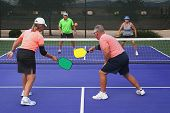 picture of pickleball  - Colorful image of two teams playing Pickleball in a mixed doubles format - JPG
