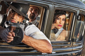 image of tommy-gun  - Group of three 1920s era gangsters shooting from car window  - JPG