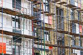 picture of scaffold  - Apartment construction in the process of being built with metal scaffolding - JPG