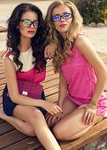 Two Beautiful Glamour Women In Bright Clothes Posing On Beach