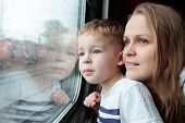 stock photo of passenger train  - Mother and son looking through a train window as they enjoy a days travel with the small boys face reflected in the glass - JPG