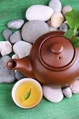 Teapot with dry flowers and herbs ingredients for tea, on stones and color wooden background