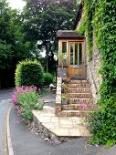 picture of english cottage garden  - Street scene of charming English country cottage with steps leading to front door and landscaped surroundings - JPG