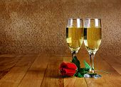 Two Glasses Of Champagne With Artificial Red Rose On Wooden Tabletop