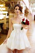 stock photo of clevage  - Beautiful young bride with a short gown and a bouquet in ger hand looking straingt - JPG