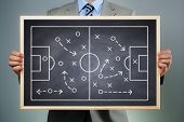 stock photo of football pitch  - Business strategy businessman holding a blackboard planning team strategy on a chalk drawing of a soccer playing field - JPG