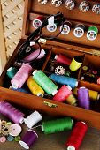 Colorful threads for needlework in wooden box on shelf in room