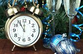 Alarm clock with Christmas tree and stemware on table close up