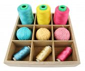 Multicolored skeins of thread in wooden box isolated on white