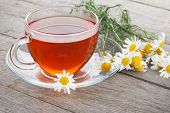Herbal tea with chamomile flowers on wooden table background