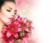 Beauty Girl with Lilly Flowers bouquet. Beautiful Model woman with Blooming pink lily flowers. Natur