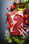 Raw beef steak with meat fork and ingredients on a dark slate background