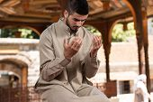 foto of muslim man  - Young Muslim Man Making Traditional Prayer To God While Wearing A Traditional Cap Dishdasha - JPG