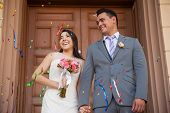 foto of boutonniere  - Happy bride and groom outside a church with confetti in the air - JPG