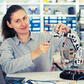 schoolgirl adjusts the robot arm model, girl in a robotics laboratory