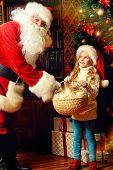 Happy little girl sitting with Santa Claus and rejoice a gift. Christmas decoration.
