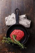 picture of ribeye steak  - Raw meat Ribeye steak and spicy herbs on cast iron frying pan on wooden background - JPG