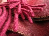 Pink fringe piled above folded scarf made in Ireland.