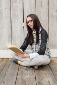 Pretty hipster reading a book against bleached wooden planks