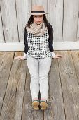 Pretty hipster sitting on ground against bleached wooden planks