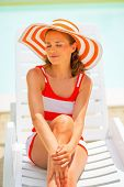 Portrait Of Relaxed Young Woman In Hat Sitting On Sunbed