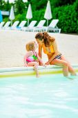 Happy Mother And Baby Girl Sitting At Poolside