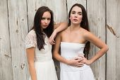 Pretty friends posing in white dresses against bleached wooden planks