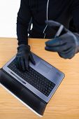Mid section of a burglar using laptop and smartphone on white background