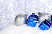 Silver and blue Christmas decorations on snow close-up