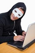 Hacker with white mask using laptop and looking at camera on white background