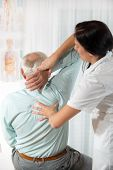 Chiropractic: Chiropractor examining senior man at office poster