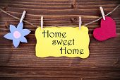 stock photo of home is where your heart is  - Yellow Tag Or Label With Heart And Flower On A Line With Life Quote Home Sweet Home On Wooden Background Two Symbols Vintage Retro And Old Fashion Style With Frame - JPG